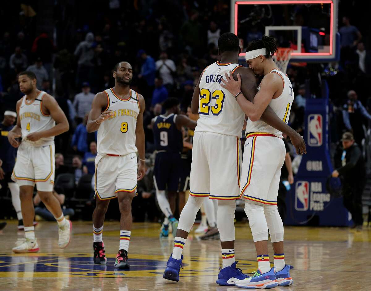 Draymond Green (23) hugs Damion Lee (1) at the end of overtime as the second half as the Golden State Warriors lost 134-131 to the Denver Nuggets at Chase Center in San Francisco, Calif., on Thursday, January 16, 2020.