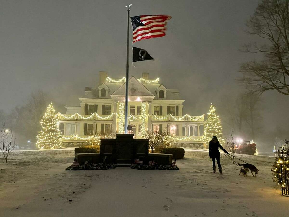 The first snowstorm of the late 2020 colder weather season is just kicking in at 7:21 p.m. Wednesday evening Dec.16, 2020, for Kevin Elston's wife Deirdre Elston and their dogs Calvin and Daisy by the Lounsbury House in Ridgefield.