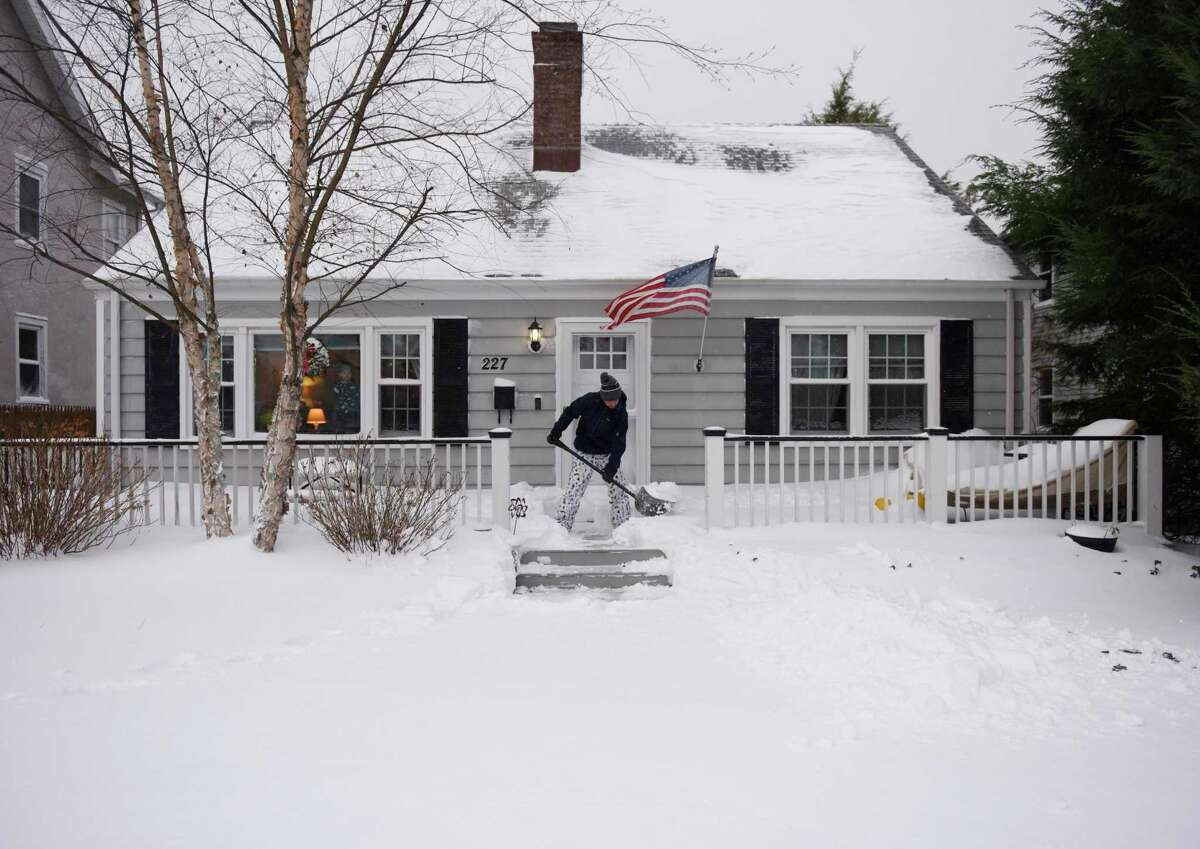 Bret John shovels snow in front of his home in Chickahominy on Thursday.