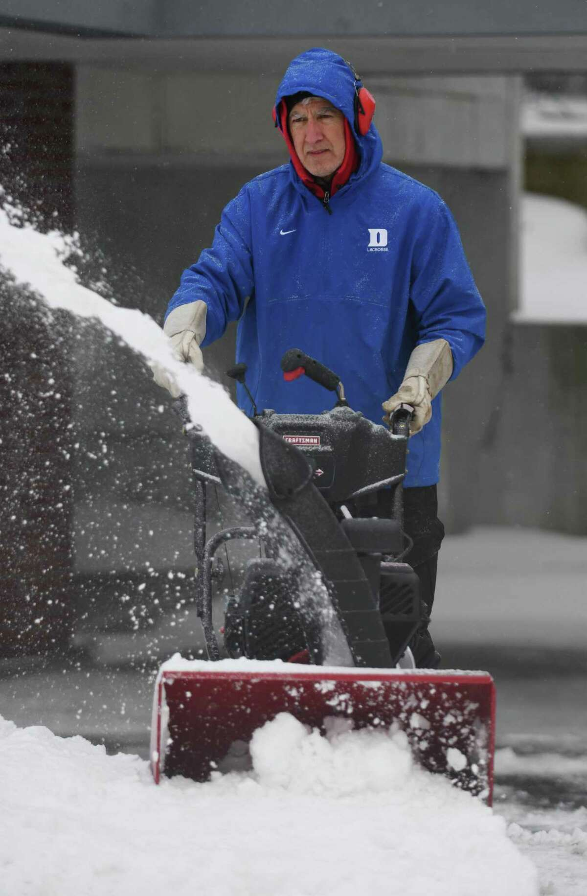 Mario Alberto uses a snowblower to clear snow from a driveway.