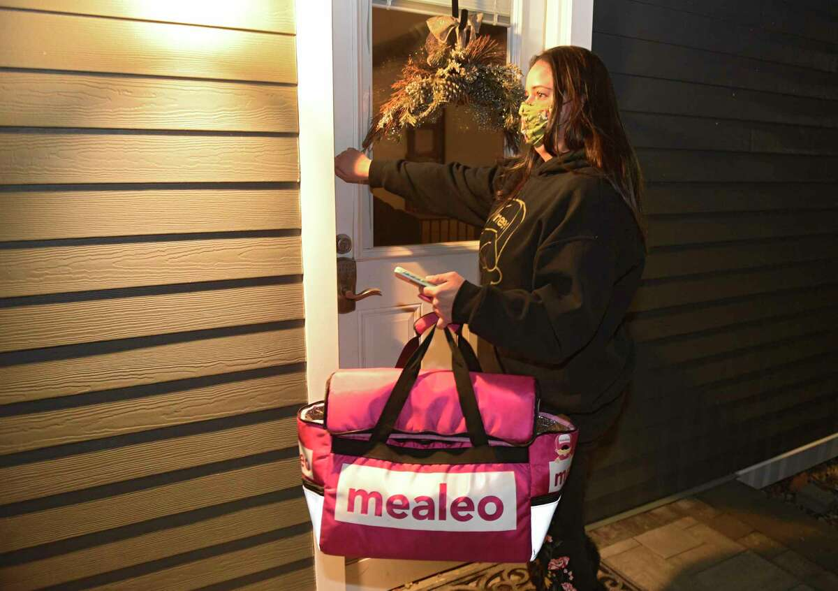 Casey Maddalla delivers an order of food from a restaurant on Wednesday, Dec. 16, 2020 in Clifton Park, N.Y. Maddalla has done more than 2,000 deliveries of restaurant food for the locally owned Mealeo app. (Lori Van Buren/Times Union)