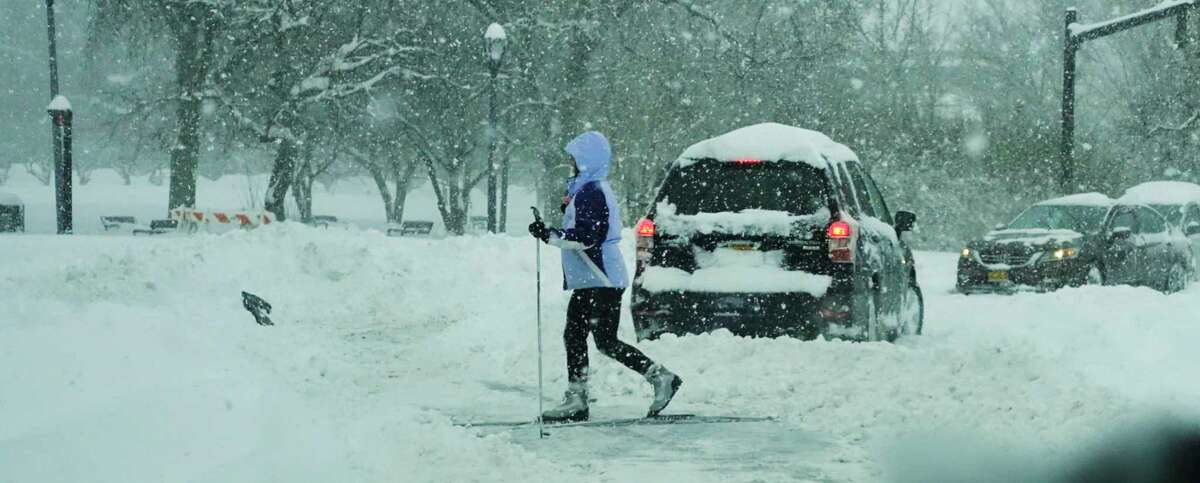 Albany Mayor Kathy Sheehan declared a snow emergency in Albany. It will mean parking restrictions on all roads in the city. In this photograph, with cars stuck in the road a woman finds an easier way to get through Washington Park on Thursday, Dec. 17, 2020, in Albany, N.Y. (Paul Buckowski/Times Union)