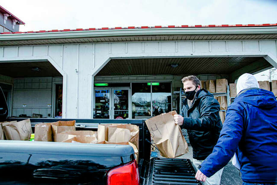 Goshen Rotarian and Glen Carbon Village Administrator Jamie Bowden, right, helps load a fellow Rotarian's truck bed Wednesday as part of the club's annual Christmas basket delivery. Photo: Tyler Pletsch   The Intelligencer