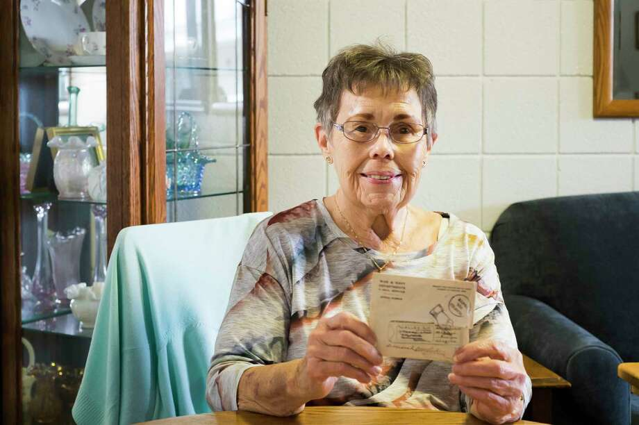 """Midland resident Betty Root poses for a portrait, holding a letter she wrote at age four to her uncle Alvin Gillett, a private in the U.S. Army who served during World War II and died of his wounds on Dec. 14, 1944. Months after she scribbled her name on the back of the envelope, the letter came back unopened, with the word """"deceased"""" handwritten on front. (Katy Kildee/kkildee@mdn.net)"""