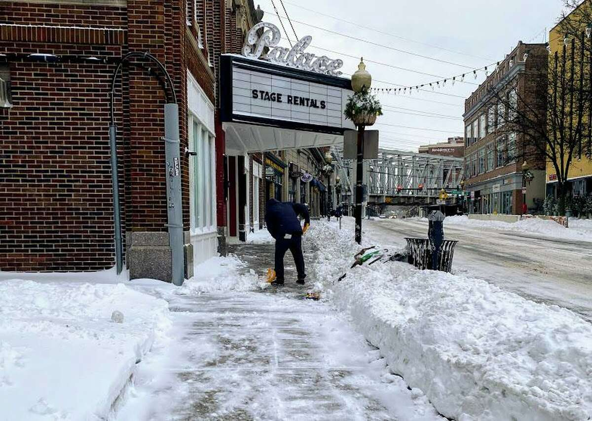 A man shovels the sidewalk outside the Palace Theater in Norwalk, Conn. on Dec. 17, 2020 after a storm brought over 5 inches of snow to the area.