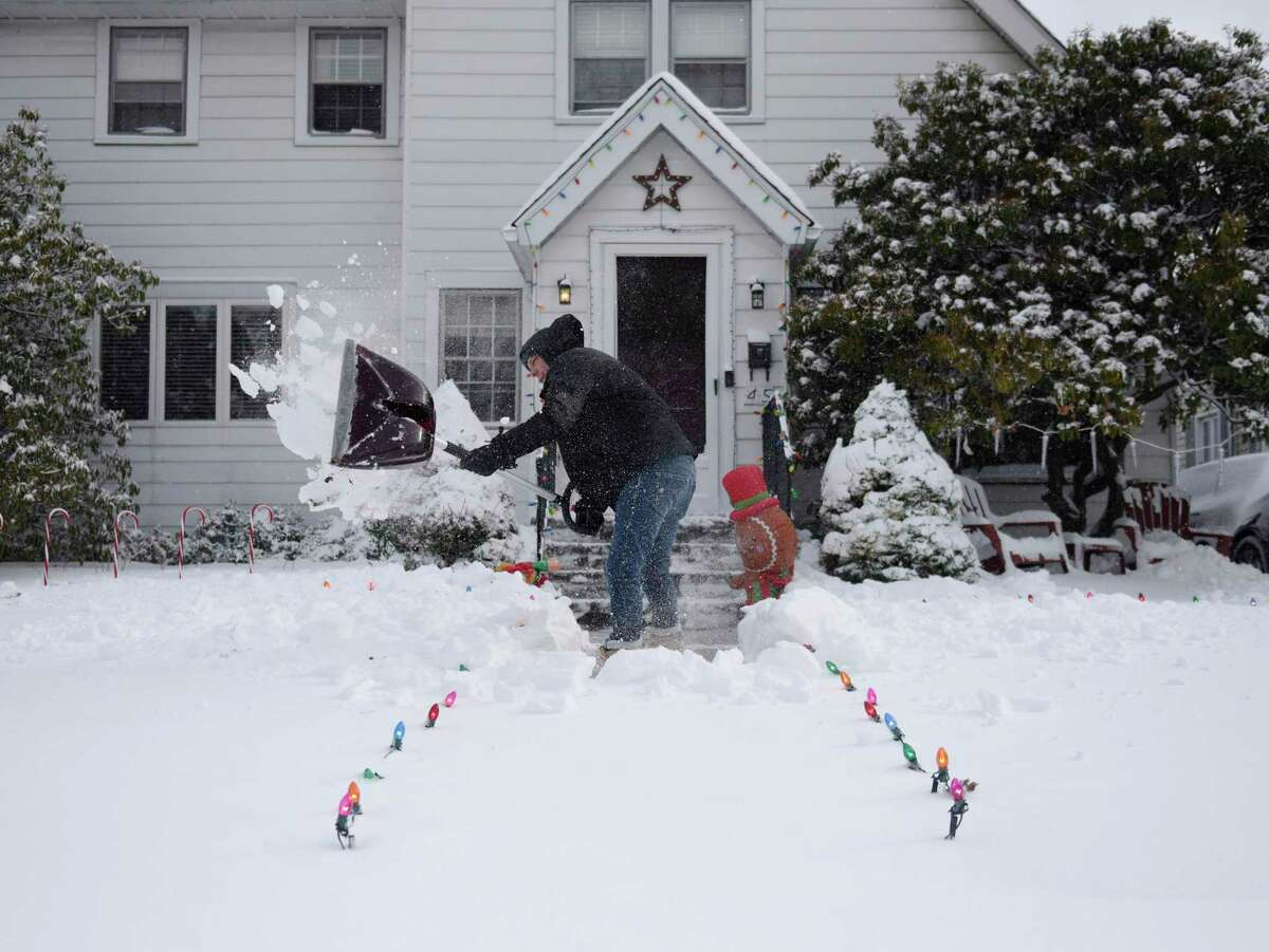 Jason Pharr digs out the walkway in front of his home in Stamford on Thursday. The area received more than half a foot of snow starting Wednesday night and continuing into the early morning hours.