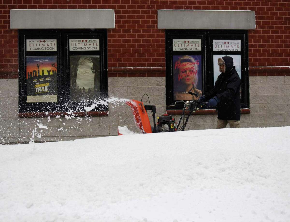 Ariel Aguilar uses a snowblower to clear snow from the sidewalk in front of Bow Tie Cinemas in Stamford, Conn. Thursday, Dec. 17, 2020. The area received more than half a foot of snow starting Wednesday night and continuing into the early morning hours.