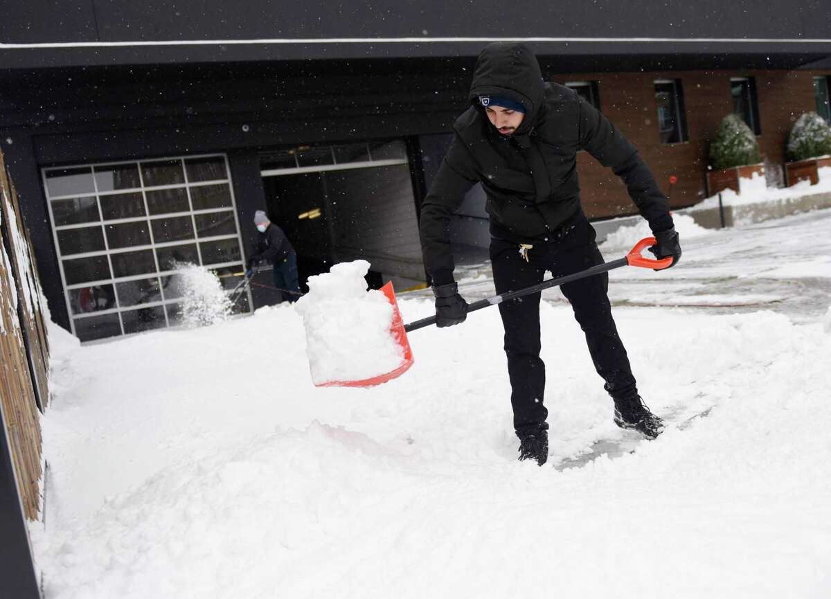 Carlos Viliccio shovels snow in front of The Lloyd in Stamford, Conn. Thursday, Dec. 17, 2020. The area received more than half a foot of snow starting Wednesday night and continuing into the early morning hours.
