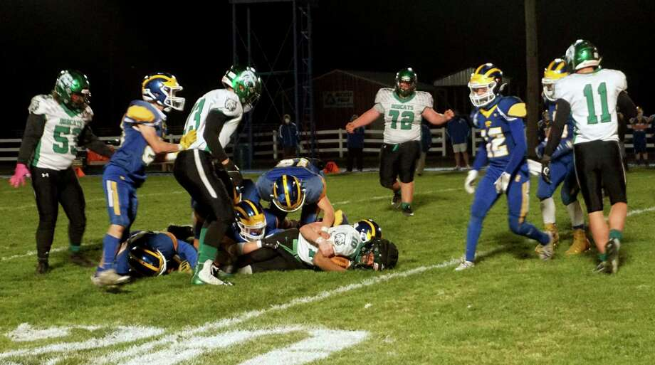 Evart defenders perform a tackle during a playoff game against Houghton Lake on Oct. 30. (Pioneer photo/Joe Judd)