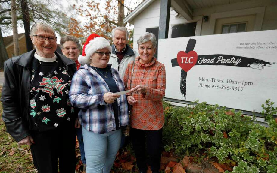Betty Emmons presents an $4,000 check to Kathy Sloan beside Marilyn Brannan, Sue Martensen and Max Martensen, at the TLC Food Pantry, Wedneday, Dec. 16, 2020, in Willis. Members of the Panorama Samaritans collected money this season for the children's shopping spree that was canceled this year due to COVID-19 and donated those funds to the pantry to reach families in need. Photo: Jason Fochtman, Houston Chronicle / Staff Photographer / 2020 © Houston Chronicle