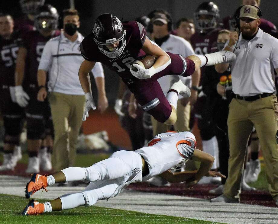 Magnolia kick rerturner Nathan Hakes, top, leaps over McKinney North's Gavin Constatine during a punt return during the first half of a 5A Division I Region II bi-district high school football playoff game, Friday, Dec. 11, 2020, in Magnolia, TX. Photo: Eric Christian Smith, FRE / Contributor / Houston Chronicle