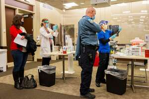 A public safety officer prepares to receive his vaccination shot at Backus Hospital where 211 doses of the Pfizer BioNTech Covid-19 vaccine were delivered and being given to 30 hospital workers on the first day of vaccinations in Norwich, Connecticut on December 15, 2020. (Photo by Joseph Prezioso / AFP) (Photo by JOSEPH PREZIOSO/AFP via Getty Images)