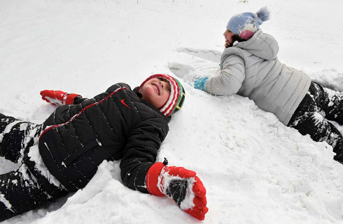 Luciano Vivenzio, 6, falls back into the fresh snow as his sister Antonia, 9, falls head first as they play after a nor'easter snow storm outside their home on Thursday, Dec. 17, 2020 in Altamont, N.Y. (Lori Van Buren/Times Union)