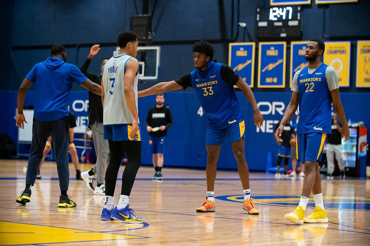 Golden State Warriors?• James Wiseman (center right) slaps hands with at Draymond Green (fat left) at practice at Chase Center in San Francisco, Calif. on Monday, Dec. 14, 2020.