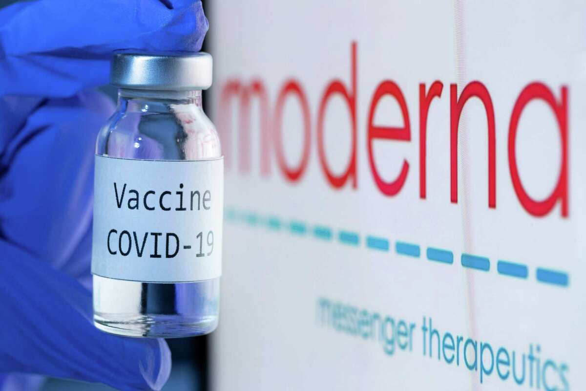 """This file photo taken on Nov. 18, 2020 shows a bottle reading """"Vaccine Covid-19"""" next to the Moderna biotech company logo."""