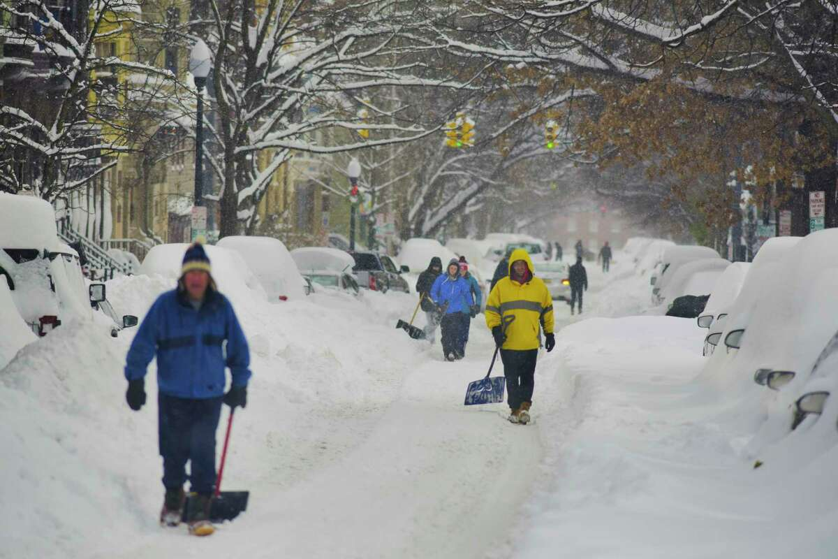 People begin the trek to their vehicles to dig them out of the snow on Thursday, Dec. 17, 2020, in Albany, N.Y. (Paul Buckowski/Times Union)