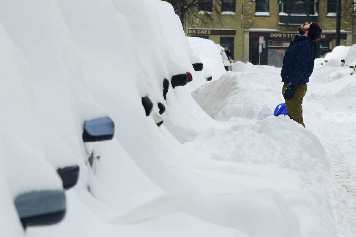Exhausted, Jack Lansing takes a short break from shoveling out his car on Thursday, Dec. 17, 2020, in Albany, N.Y. (Paul Buckowski/Times Union)