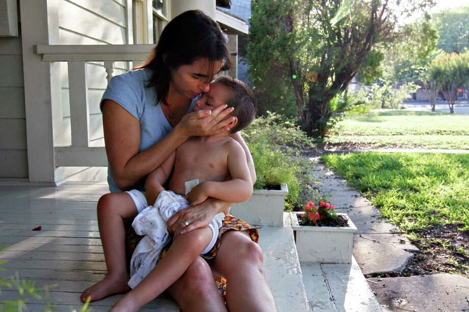 Liz Tullis comforts her son Conrad, 3, before bed on the porch of their Monte Vista home. Conrad nearly drowned as a toddler while under the care of his paternal grandfather. He suffered major brain damage and needs constant attention. Photo: NICOLE FRUGE, SAN ANTONIO EXPRESS-NEWS / SAN ANTONIO EXPRESS-NEWS