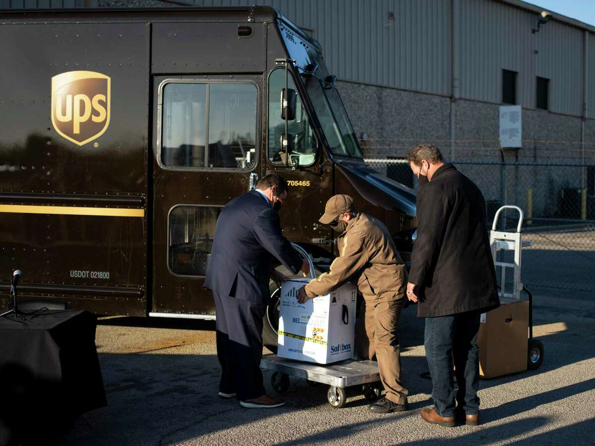 An employee of UPS unloads a box containing 5000 doses of the Pfizer-BioNTech COVID-19 vaccine to be delivered to Dell Seton Medical Center in Austin during a press conference on Texas?• vaccine distribution plan at a UPS distribution facility in Austin, Tx., U.S., on Thursday, December 17, 2020.