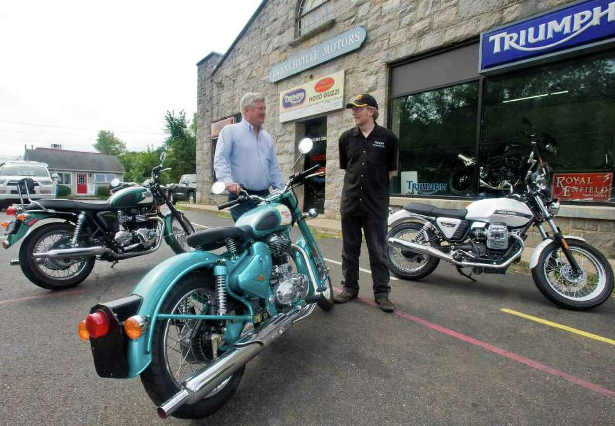 Branchville Motors owner Alex Gifford, left, chats with Ben Armstrong, who oversees public relations. The two are surrounded by a Triumph Bonneville 865cc, a Royal Enfield 500cc and a Moto Guzzi Classic 750cc, all 2010 models. Wednesday, Aug. 25, 2010