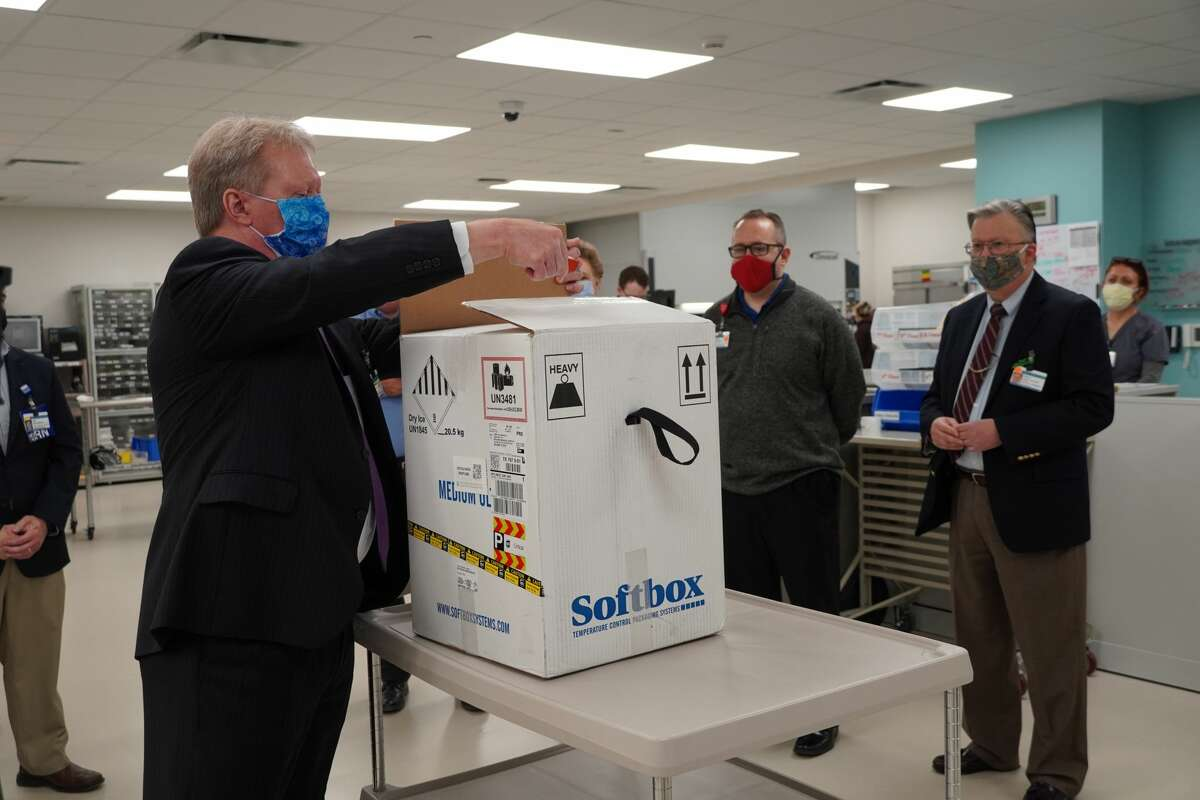 Midland Health President and CEO Russell Meyers opens up the box of COVID-19 vaccine Thursday morning at Midland Memorial Hospital.