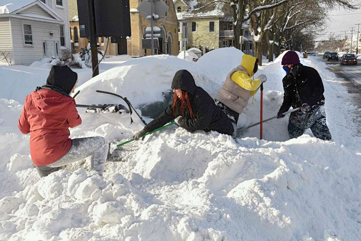 From left, Albany friends Emily McCord, Sara Eads, Alexis Desjarden and Kasey Palmer work on digging out Alexis' car on Madison Ave. after a nor'easter snow storm on Thursday, Dec. 17, 2020 in Guilderland, N.Y. The friends were going to tackle the next persons car afterwards. (Lori Van Buren/Times Union)