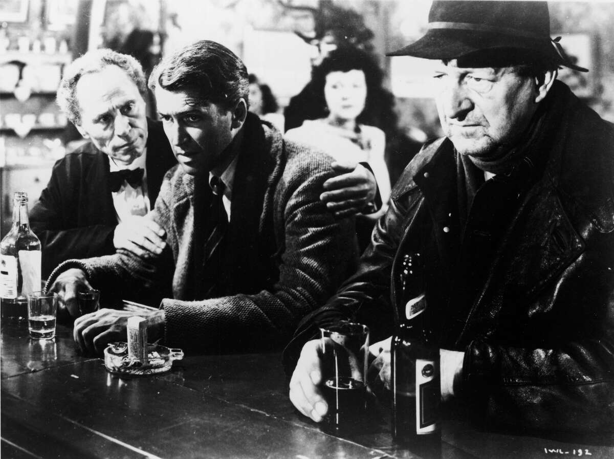 American actor Jimmy Stewart, center, sits glumly at a bar in a scene from the film