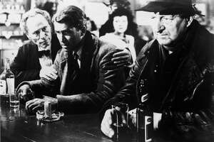 American actor James Stewart (1908 - 1997) (center) sits glumly at a bar in a scene from the film 'It's a Wonderful Life,' directed by Frank Capra, California, 1946. (Photo by RKO Pictures/Courtesy of Getty Images)