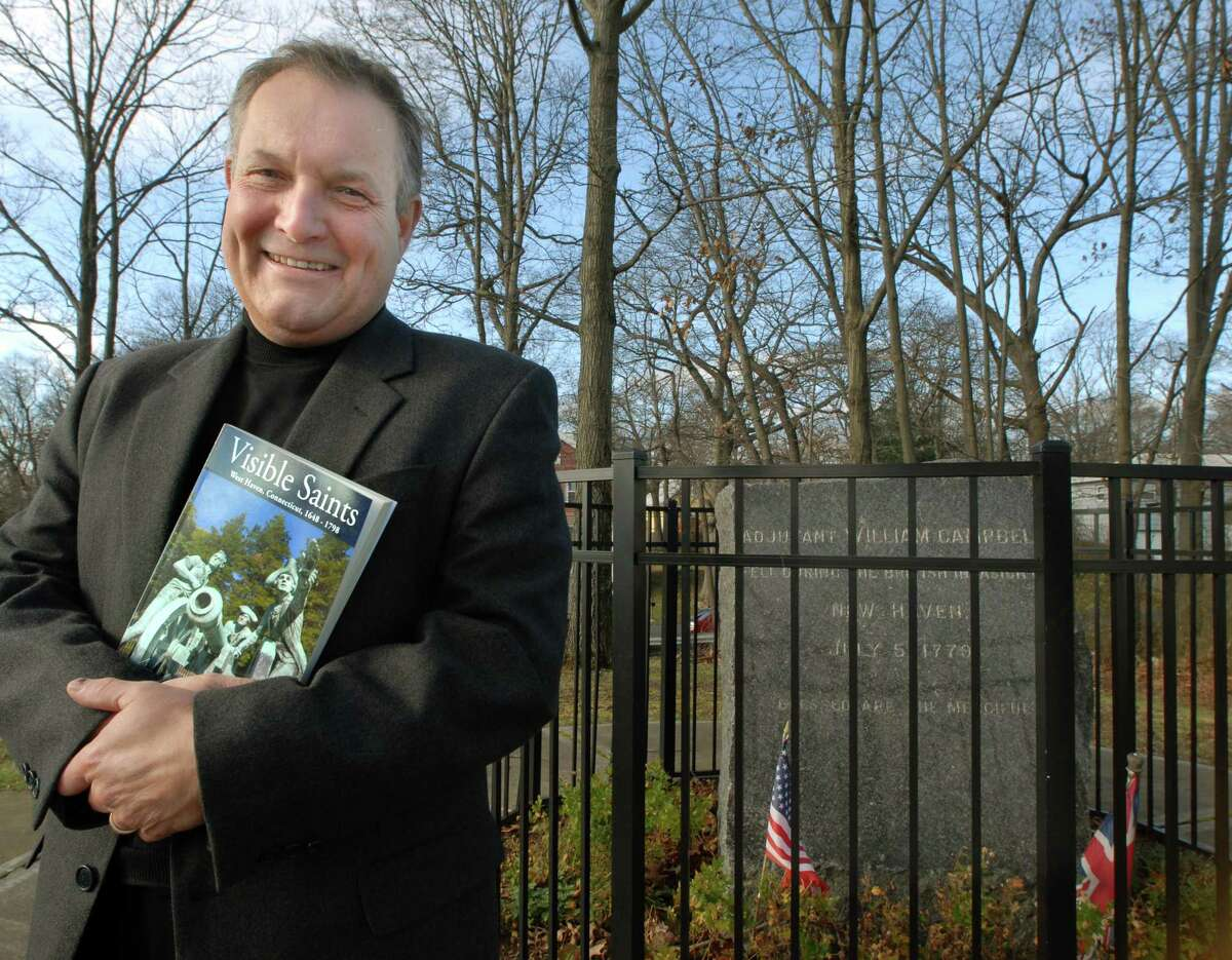 """Peter Malia with his earlier book """"Visible Saints"""" in 2009 near the monument denoting the burial place of Revolutionary War British soldier William Campbell at the edge of the University of New Haven campus."""