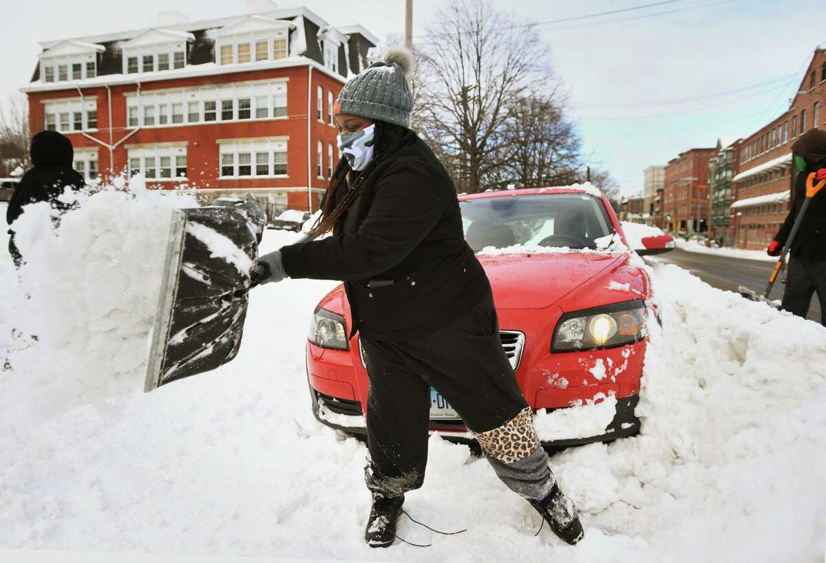 Lela Ndikumana, of Shelton, digs out a car in the aftermath of Thursday morning's snow on Howe Avenue in Shelton, Conn. on Thursday, December 17, 2020.