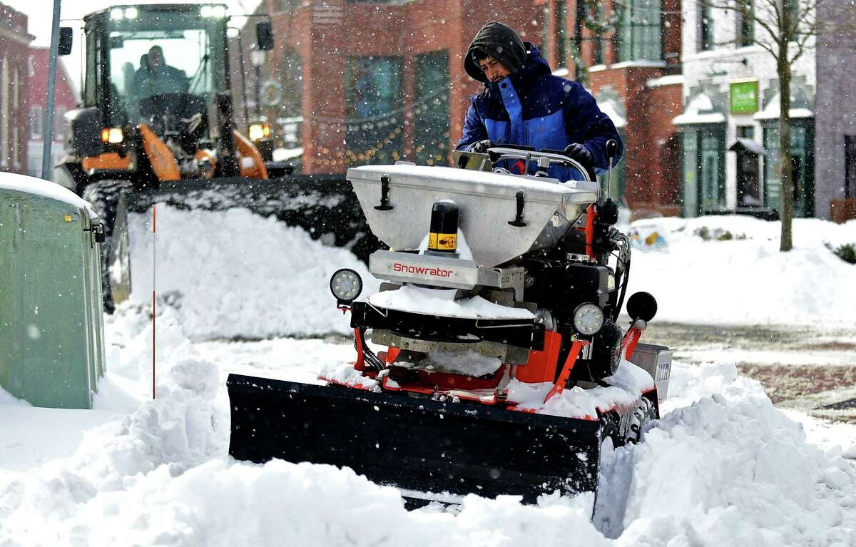 Workers with Niro contractors clear sidewalks downtown following the snowstorm Thursday, December 17, 2020, in Westport, Conn.