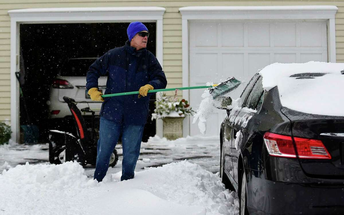 Mike Perry cleans the snow off his vehicle outisde his home on Sylvan Road following the snowstorm Thursday, December 17, 2020, in Westport, Conn.
