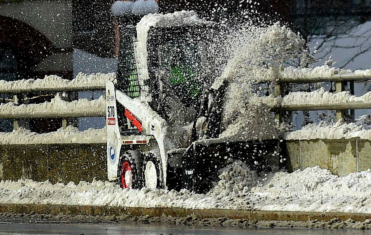 Contractors with the Town of Westport clear snow from the Ruth Steinkraus bridge following the snowstorm Thursday, December 17, 2020, in Westport, Conn.