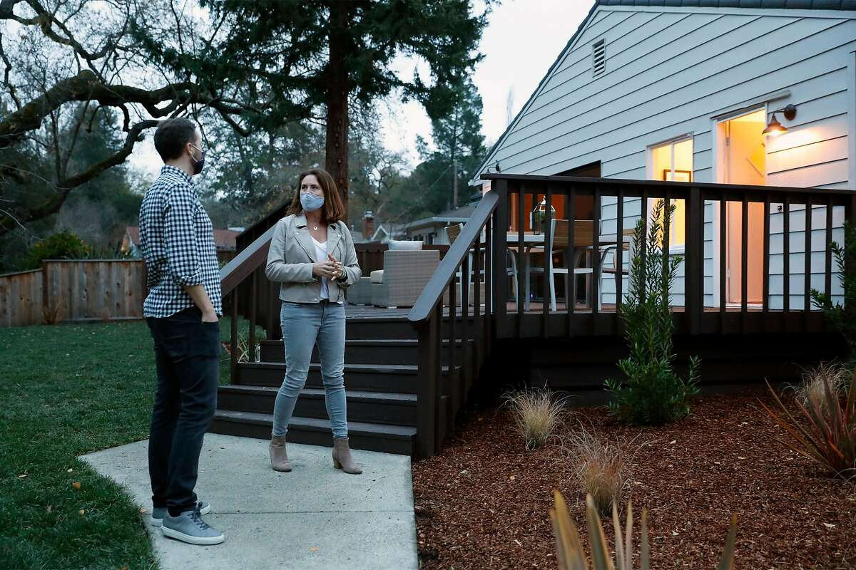 Real estate agent Linette Edwards gives Jonny Price a tour of a single family home for sale on Orchard Court in Orinda, Calif., on Wednesday, December 16, 2020.