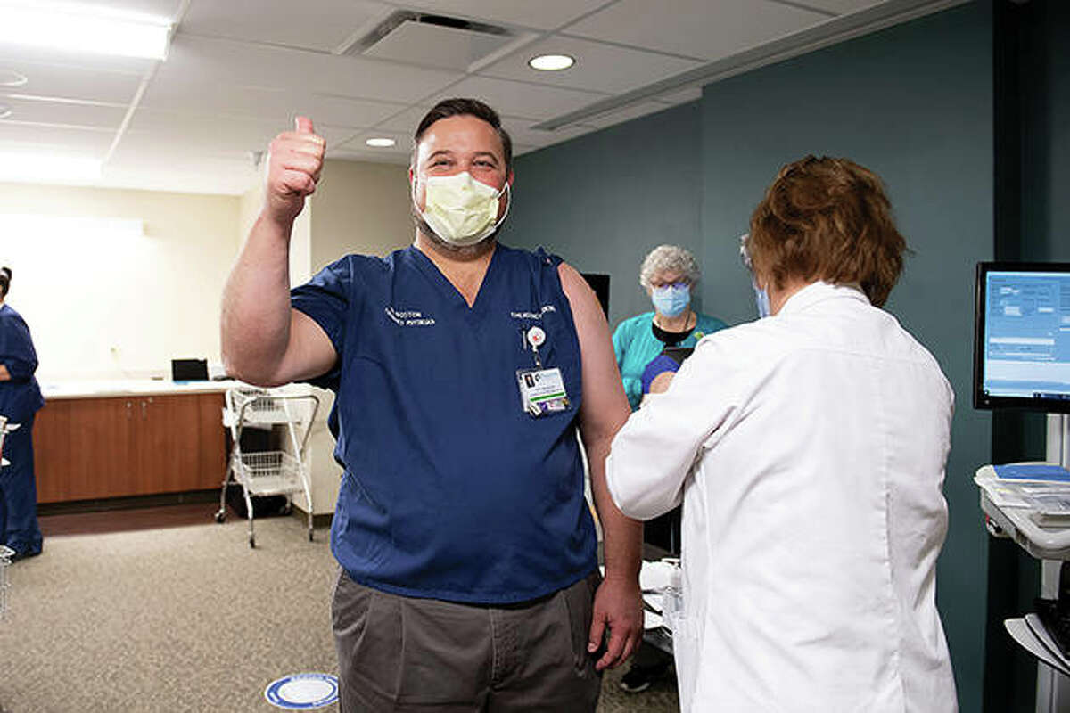 Passavant Area Hospital President Scott Boston gives a thumbs-up sign as he receives a COVID-19 vaccination Thursday.