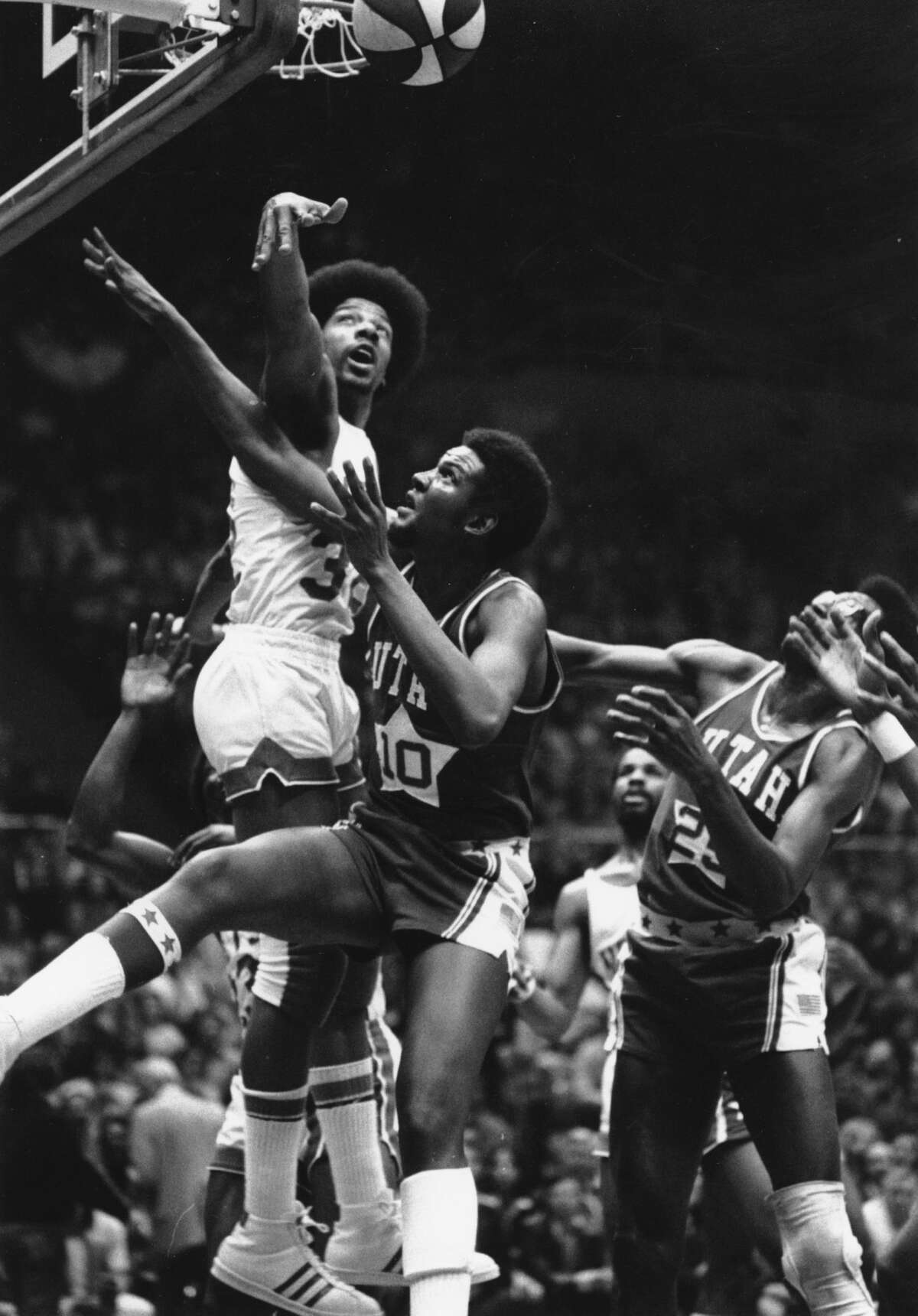 Julius Erving (32), of the New York Nets, is seen jumping high for a block during the ABA Championship Series against the Utah Stars at the Nassau Coliseum in Uniondale, N.Y., on May 4, 1974. Trying for the rebound for the Stars is Bruce Seals (10). (AP Photo/Richard Drew)