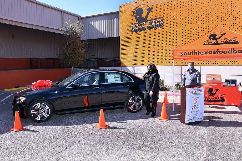 South Texas Food Bank Executive Director Alma Boubel and Ruben Villarreal stand next to the 2020 Mercedes-Benz that was the top prize in the Hunger Relief Holiday Raffle held Wednesday, Dec. 16. Photo: Cuate Santos / Laredo Morning Times / Laredo Morning Times