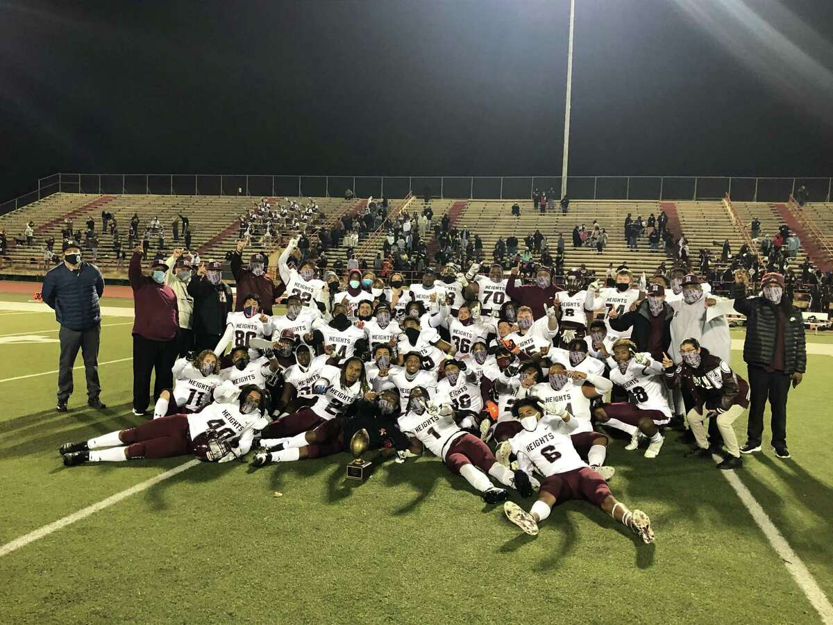 The Heights Bulldogs pose triumphantly with the trophy after beating Bellaire 35-20 on Dec. 4 to wrap up an undefeated District 18-6A championship