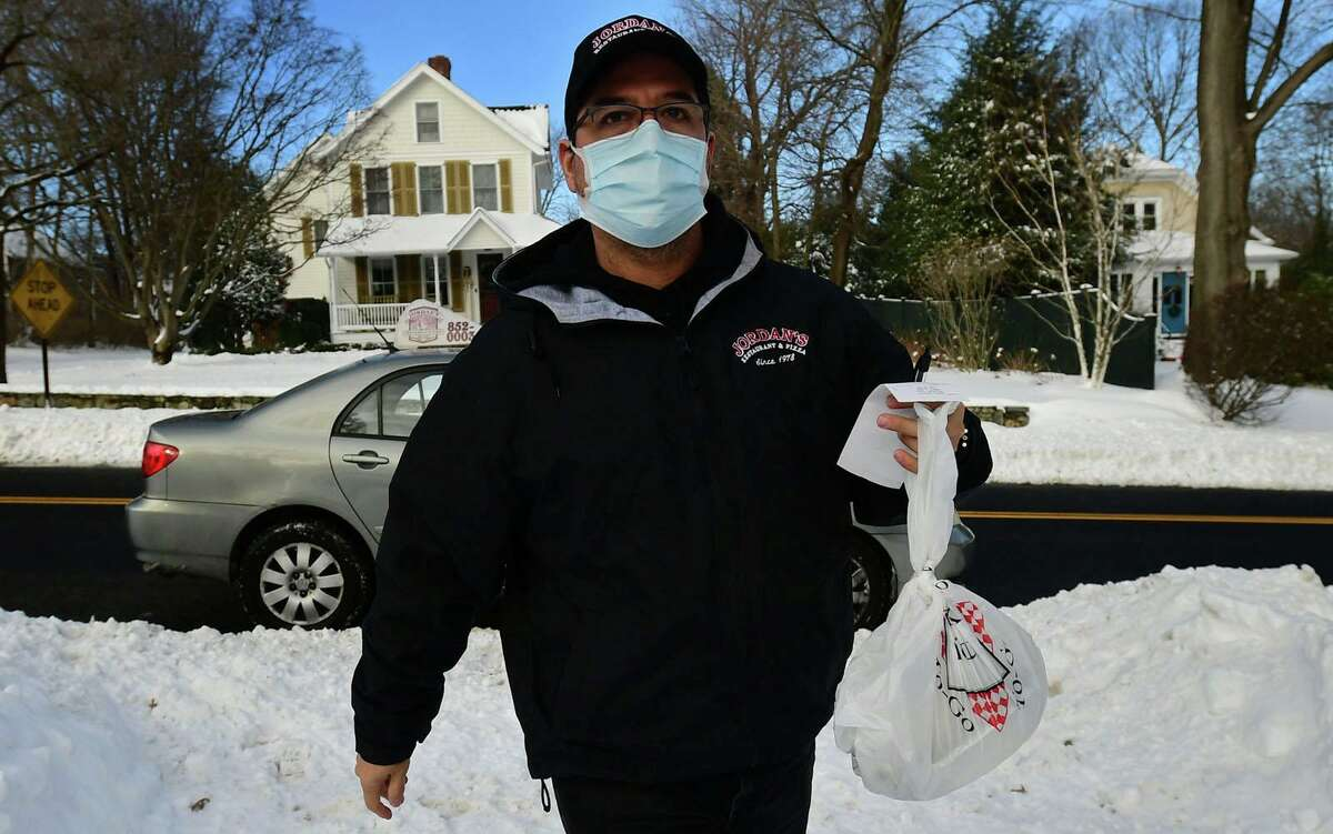 David Caceres, delivery driver for Jordan's Pizza, makes his rouds Thursday, December 17, 2020, in Norwalk, Conn. Delivery drivers have to navigate difficulties during snow storms and their aftermaths.