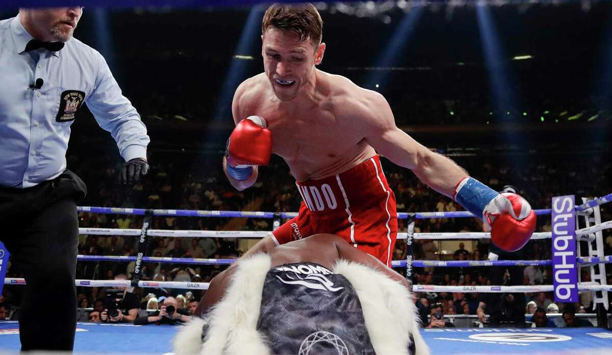 FILE - In this Saturday, June 1, 2019 file photo, England's Callum Smith, above, knocks down Hassan N'Dam, of France, during the first round of a super middleweight championship boxing match in New York. Canelo Alvarez will return to the ring in a world super-middleweight title fight against Britain's Callum Smith on Dec. 19, the boxers announced early Wednesday, Nov. 18, 2020. (AP Photo/Frank Franklin II, File)