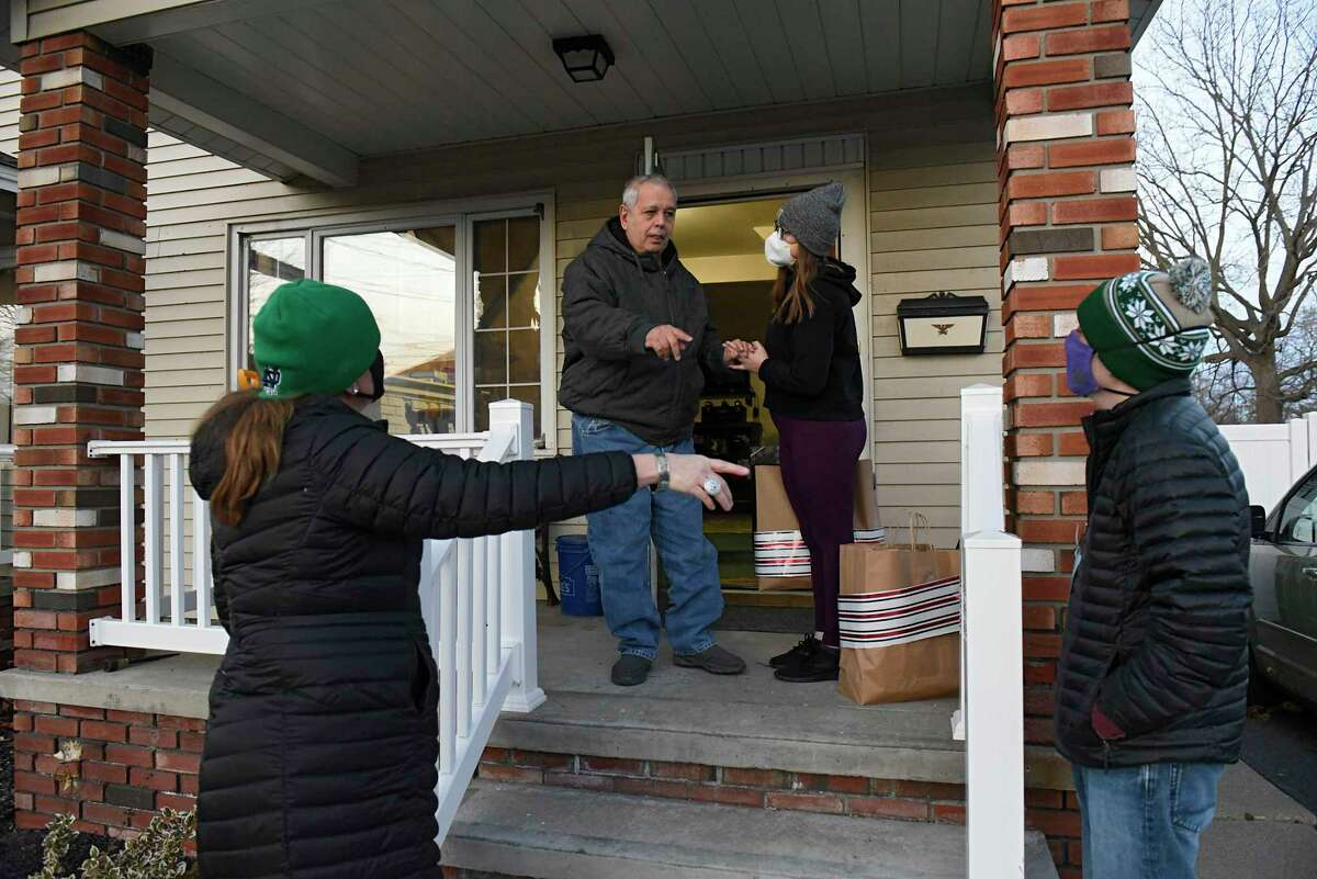 Maureen O'Brien, left, a volunteer with New York State Industries for the Disabled, talks to resident Frank, second from left, and ARC supervisor Sydney Waddell as she and her son Gabe Donovan, right, deliver meals on Tuesday, Dec. 15, 2020, to residents of a group home the Schenectady ARC runsin Schenectady, N.Y. (Lori Van Buren/Times Union)