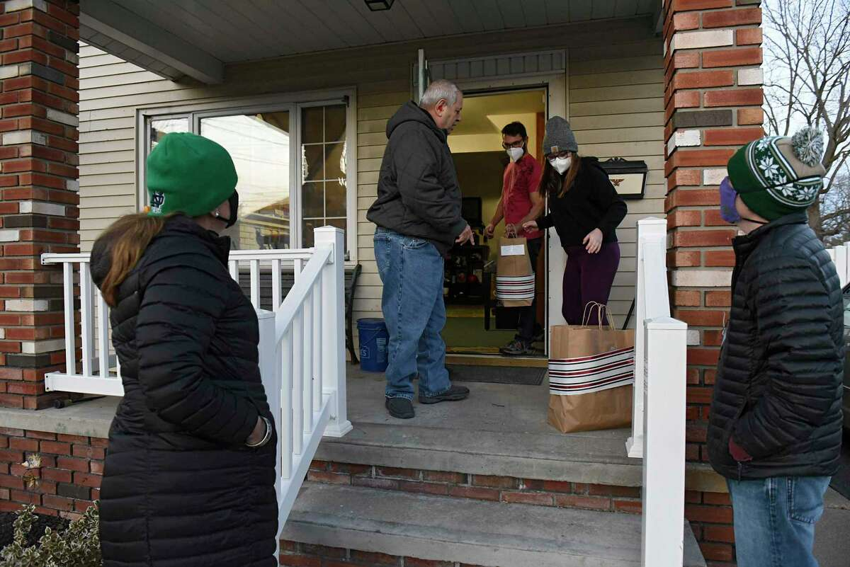 New York State Industries for the Disabled Volunteer Maureen O'Brien, left, says goodbye to resident Frank, second from left, and ARC supervisor Sydney Waddell as she and her son Gabe Donovan, right, deliver meals to residents of a group home the Schenectady ARC runs on Tuesday, Dec. 15, 2020 in Schenectady, N.Y. (Lori Van Buren/Times Union)