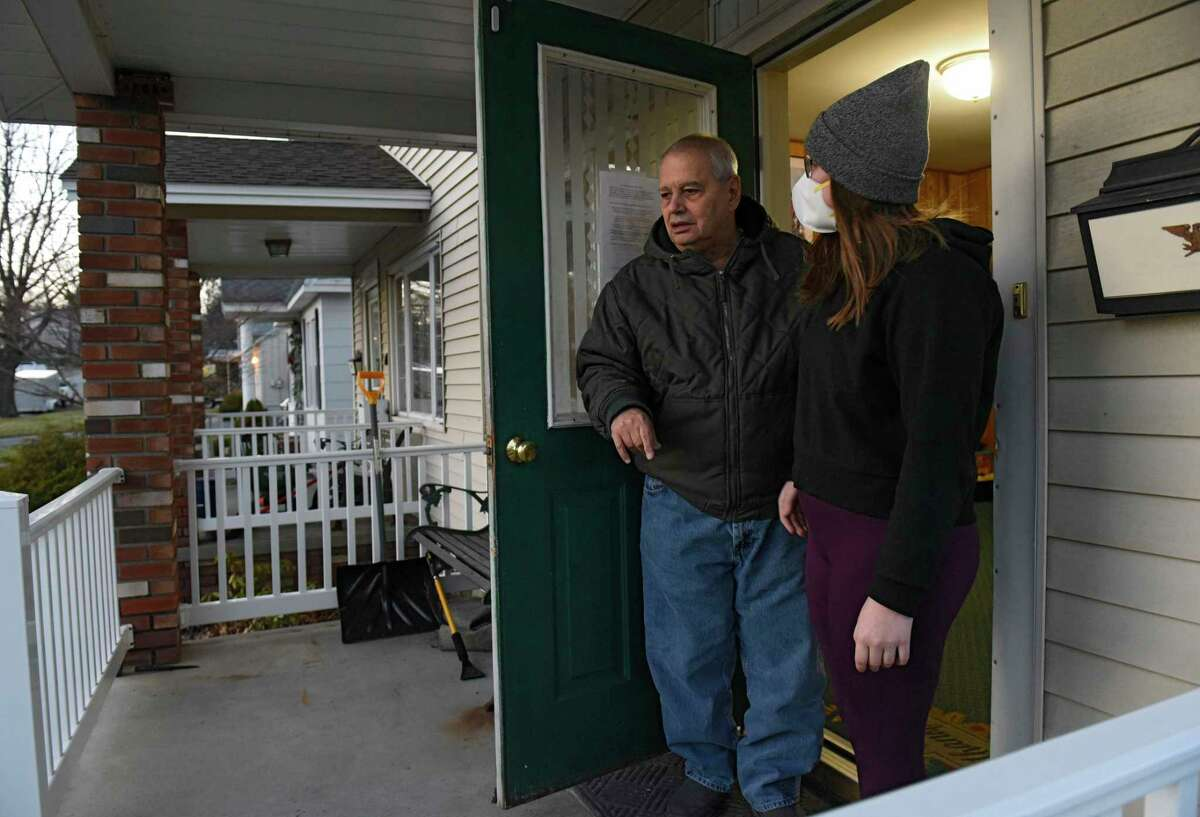 Frank, left, a resident at a group home run by the Schenectady ARC, stands in the doorway with ARC supervisor Sydney Waddell as volunteers deliver meals to the home on Tuesday, Dec. 15, 2020, in Schenectady, N.Y. (Lori Van Buren/Times Union)