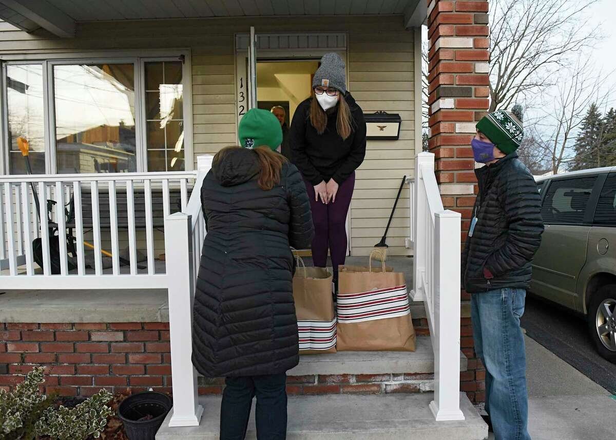 New York State Industries for the Disabled Volunteer Maureen O'Brien, left, talks to ARC supervisor Sydney Waddell as she and her son Gabe Donovan, right, deliver meals to residents of a group home the Schenectady ARC runs on Tuesday, Dec. 15, 2020 in Schenectady, N.Y. (Lori Van Buren/Times Union)