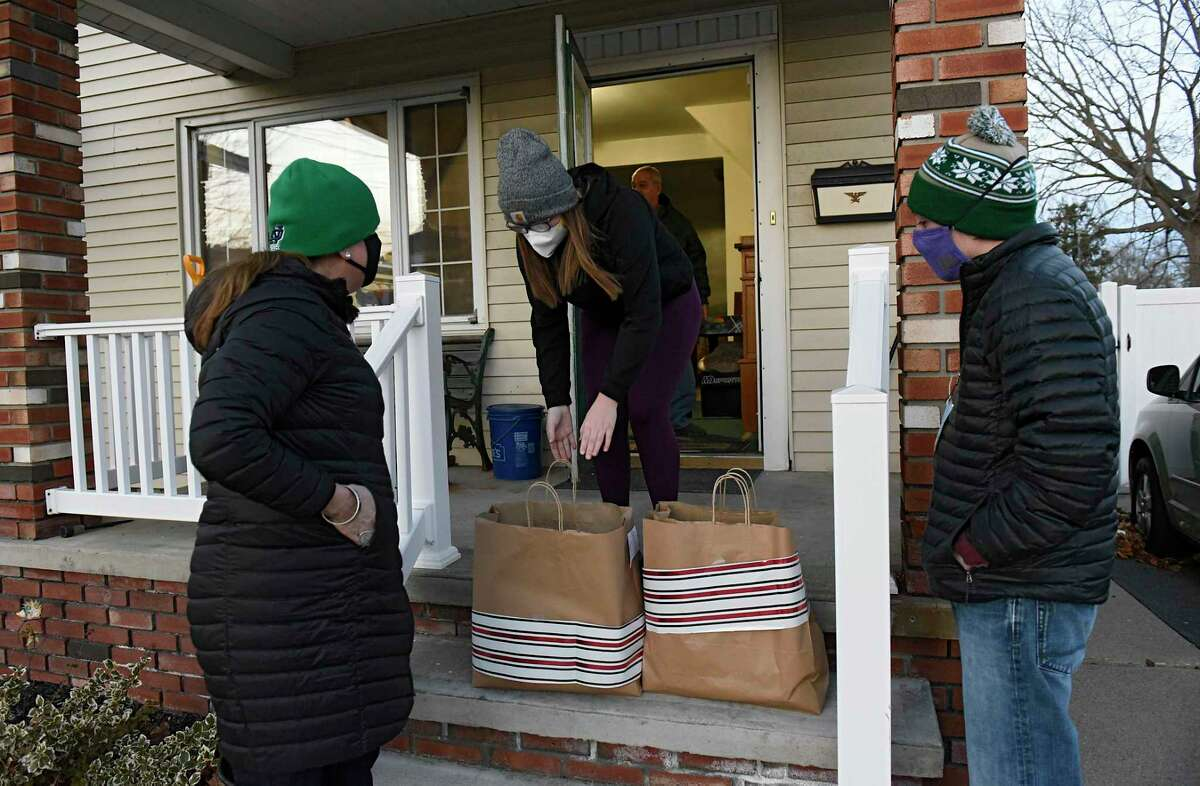 Maureen O'Brien, left, a volunteer with New York State Industries for the Disabled Volunteer, talks to ARC supervisor Sydney Waddell as she and her son Gabe Donovan, right, deliver meals to residents of a group home on Tuesday, Dec. 15, 2020, that the Schenectady ARC runs in Schenectady, N.Y. (Lori Van Buren/Times Union)