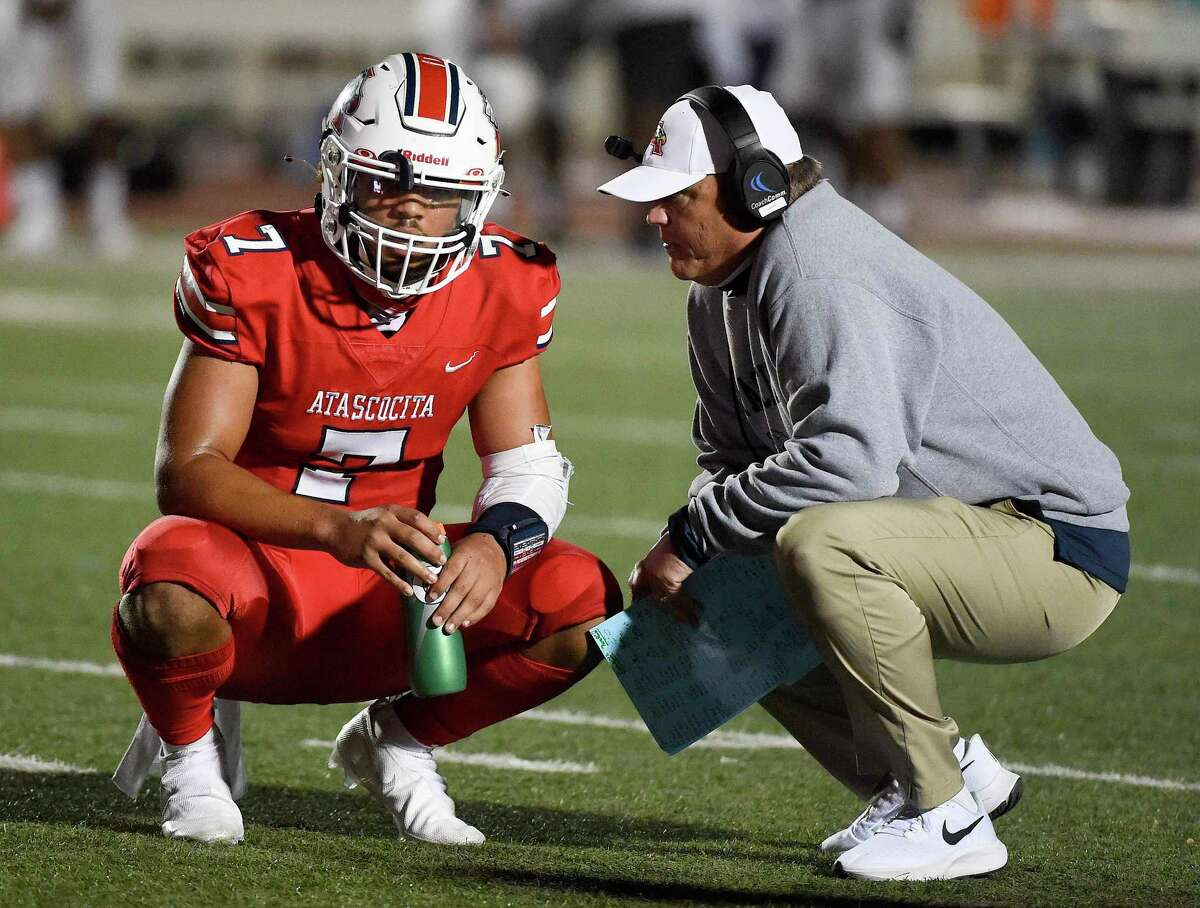 Atascocita head coach Craig Stump, right, talks with quarterback Gavin Session after Session's touchdown during the second half of a high school football game against Humble, Friday, Oct. 23, 2020, in Humble.