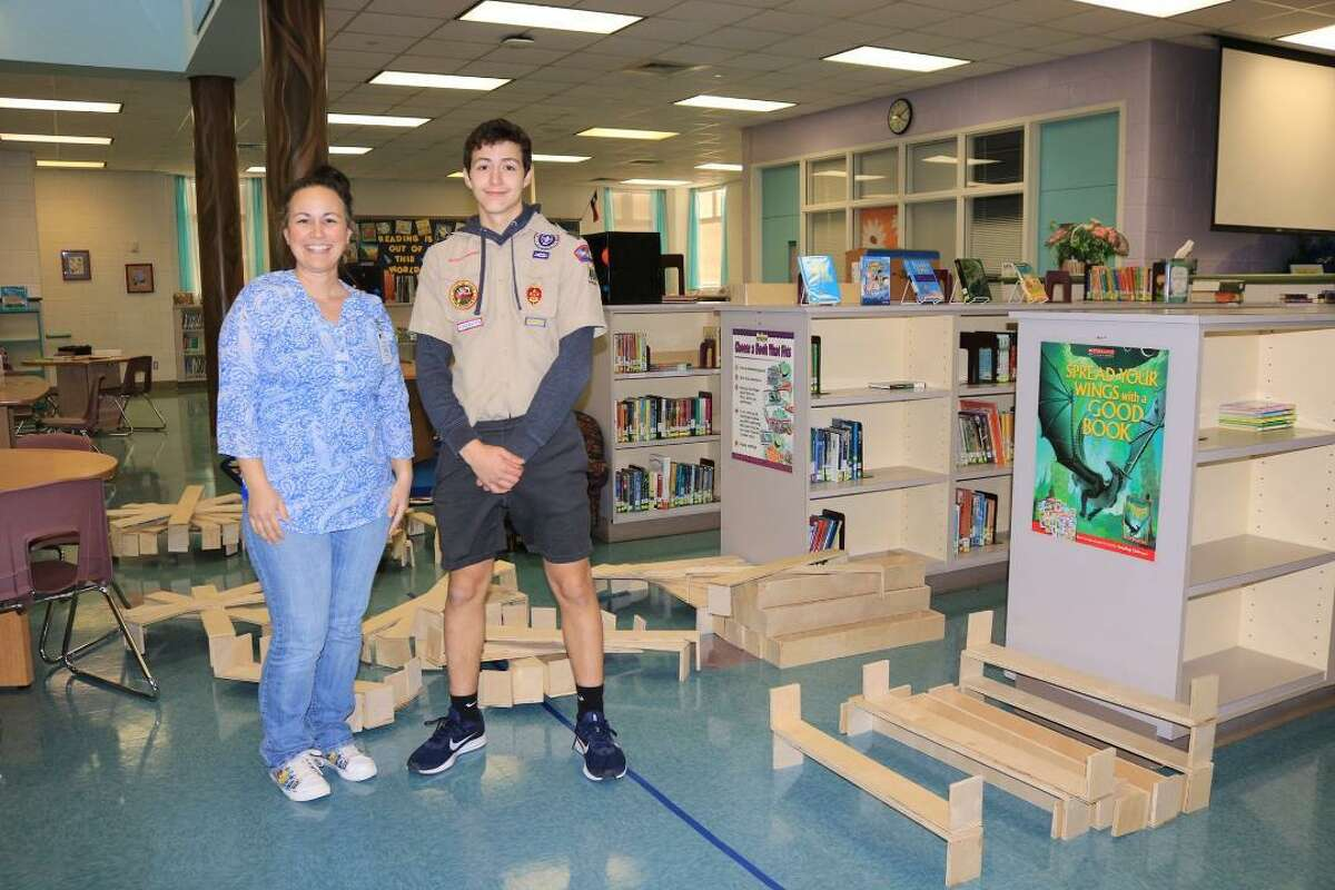 Cooper, shown with Jenni Murphy, former librarian at Challenger Elementary School, also built 130 plywood spacers to insert in the school's library shelves to prevent kids from pushing books too far back.