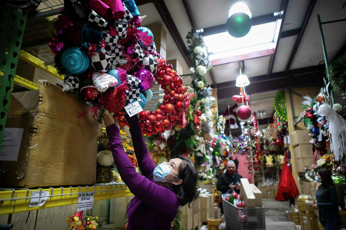 Tina Rubio straightens a wreath she made for a client at Craftex, a decoration supply store on Monday, Dec. 14, 2020. Rubio has been designing at Craftex for sixteen years.