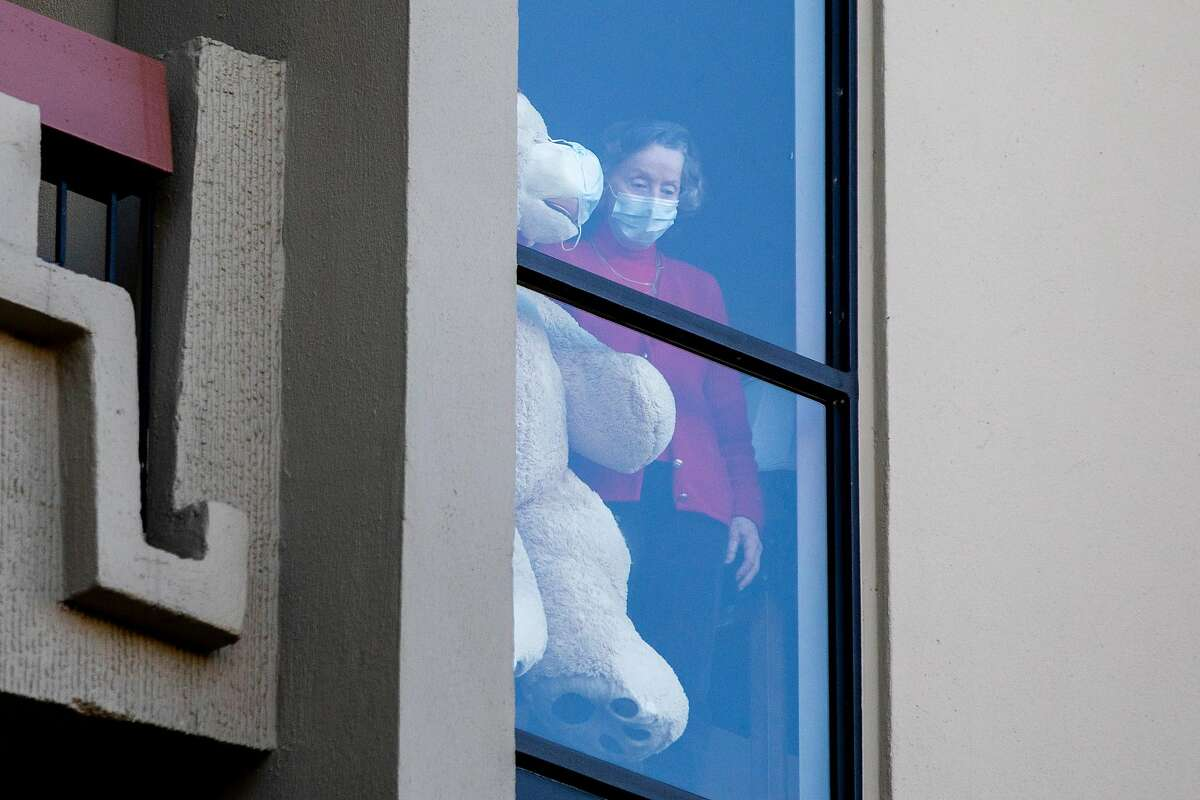 A resident watches from a window as staff begin to receive the Pfizer COVID-19 vaccine at the Tamalpais Marin assisted living facility in Greenbrae.