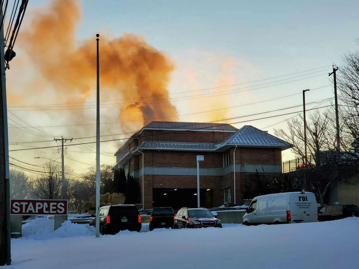 Greenwich firefighters worked to extinguish a fire Thursday, Dec. 17, 2020 after a vehicle crashed into a store at the Thruway Shopping Center on East Putnam Avenue in the Riverside section of Greenwich, Conn. The driver of the car died, according to police.